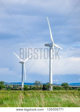 Windmills standing in fields during summer day