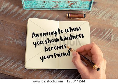 Retro effect and toned image of a woman hand writing on a notebook. Handwritten quote An enemy to whom you show kindness becomes your friend as inspirational concept image