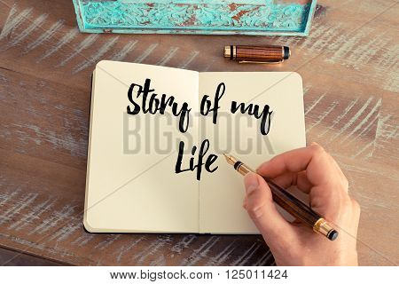 Retro effect and toned image of a woman hand writing on a notebook. Handwritten quote Story Of My Life as inspirational concept image