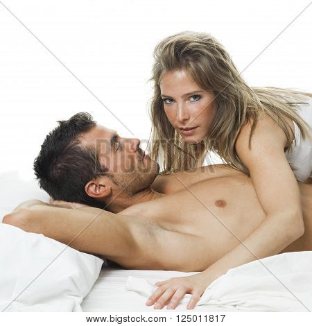 a man and a woman foreplaying in a white bed