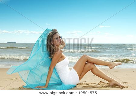 woman laying on sand sea