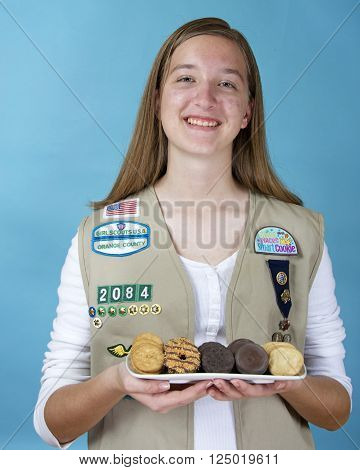 ALAMEDA CA - FEBRUARY 18 2016: Cadette Girl Scout Meaghan Fitzgerald holding a white rectangular plate with the five most popular original Girl Scout cookies created by ABC Bakers.