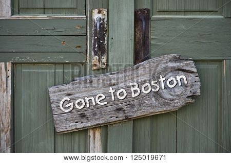 Gone to Boston sign on old green doors.