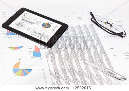Business performance analysis. Business Graphs with tablet, pen, glasses.