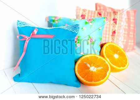 aromatherapy pillows, aromatization space. Four small decorative pillows pale blue and pink with lace. Handmade. White wooden background and orange halves. Vitamins for a good mood.