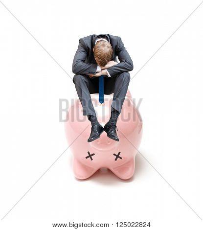A sad businessman on a dead piggy bank