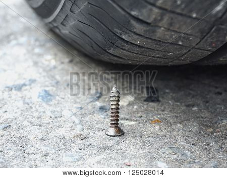 Sharpen metal screw nail nearly to puncture into wheel tire, selective focus (colored filter effect)