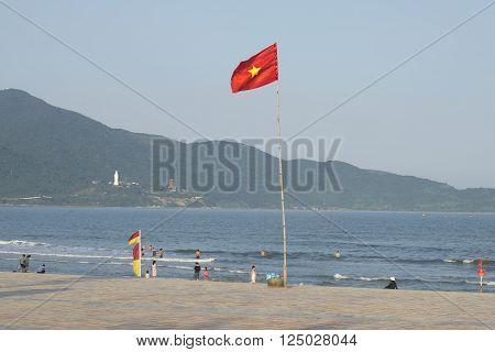 DA NANG, VIETNAM - JANUARY 05, 2016: Vietnamese flag on the beach We Khe. People relax and swim on the best beach in Da Nang, Vietnam