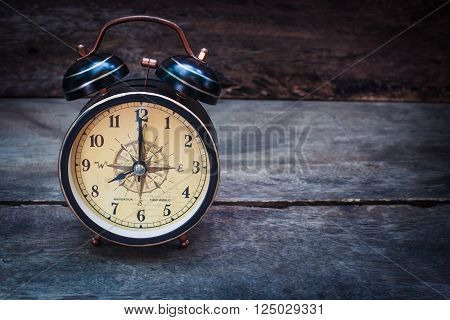 Still life with alarm clock on wood table ( alarm clock show 8 o`clock ).