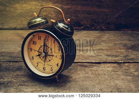 Still life with alarm clock on wood table ( alarm clock show 8 o`clock ).