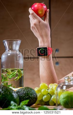 Female hand with smart watch showing calories and green fruits on the foreground. Smart watch technology for healthcare