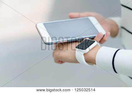 Woman connect with cellphone and smart watch