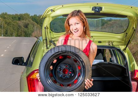 Portrait Of A Beautiful Girl Holding A Spare Wheel Of A Car