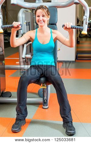 Beautiful Slender Girl Is Engaged On A Simulator In The Gym