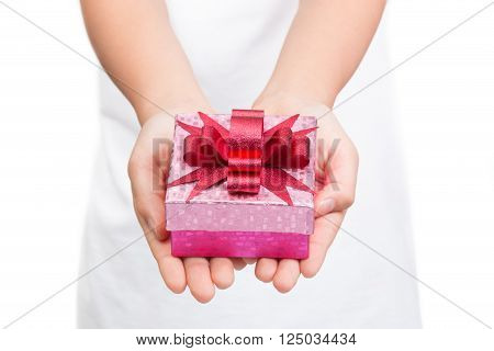 Girl's hands holding shinny pink box of present with shinny red bow on top white shirt white background selective focus on the bow and box leaving shirt and background out of focus