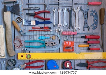 The tools laid out on a wooden floor top view. Locksmith and carpentry tools.