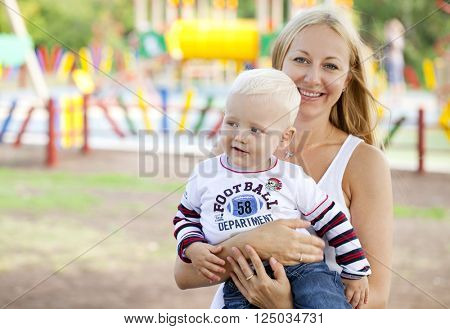 Beautiful young mother holds on hands of his two year old son in summer park