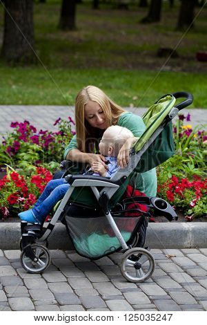 Young mother with two year old son in summer park