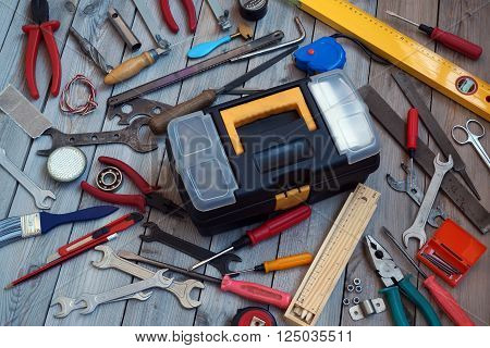 Tool box and tools scattered around him on the wooden floor top view. Locksmith and carpentry tools.