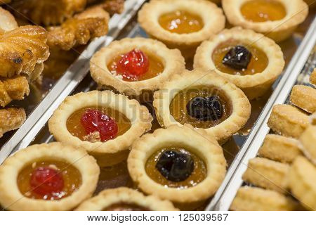 pastries decorated with red cherries and jam