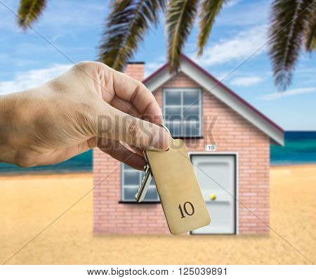 guest holding the apartment house key with palm and beach in background