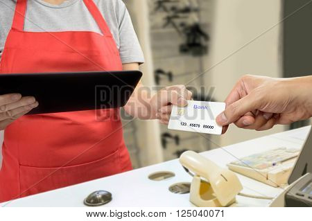 man handing over her credit card to a salesperson to pay