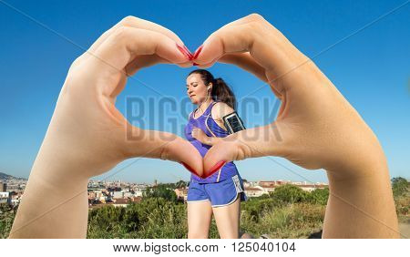 woman making the heart shape with her hands on athlete in concept of love of sport