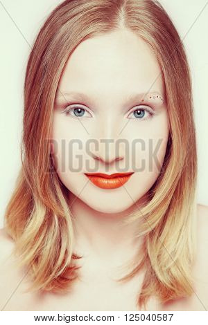 Vintage style portrait of young beautiful smiling blond girl with orange lipstick and fancy make-up