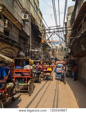 DELHI INDIA - 19TH MARCH 2016: A view along streets of central Delhi showing Rickshaws buildings and people.