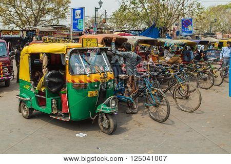 DELHI INDIA - 19TH MARCH 2016: Tuk Tuk Rickshaws parked on a street in central Delhi during the day. People can be seen.