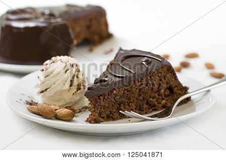 sacher cake slice on plate with fresh cream and almonds