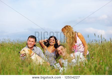 friends and dog in green grass