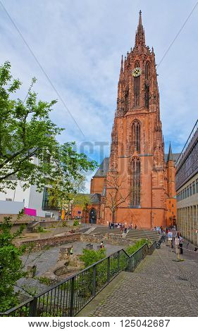 FRANKFURT GERMANY - APRIL 29 2012: Frankfurt Cathedral and Roman ruins in Frankfurt in Germany. It is also called Frankfurter Dom or Cathedral of Saint Bartholomew. Tourists nearby