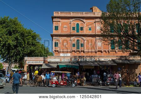 JAIPUR INDIA - 23RD MARCH 2016: A view of buildings in the Pink City part of Jaipur during the day. Buildings Rickshaws people and a cow can be seen.