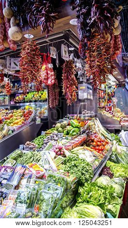 SPAIN, BARCELONA, JUNE, 29, 2015 - La Boqueria market with vegetables and bundles of hot peppers in Barcelona, Spain. La Boqueria market, Europe's largest and most famous food markets.