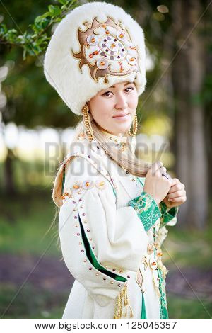 Portrait of girl in traditional festive attire, steppe nomad peoples, outdoors. looking in the camera.