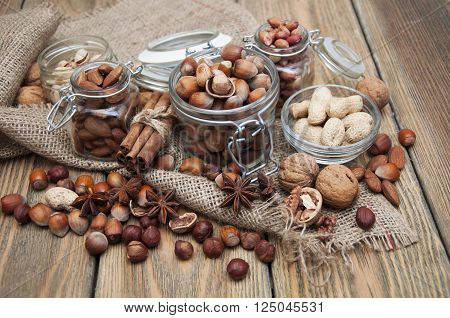 Variety of nuts: walnut hazelnut hazelnuts peanuts pine nuts and other with spices on a wooden background