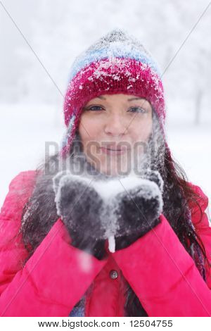 winter girl blow on snow