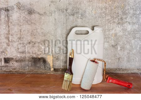 Home interior room repair concept - old gray concrete wall and dirty brown floor in repairing room with white plastic can paint roller and brush near the wall close-up view