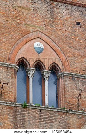 The typical three-part Sienese gothic windows of San Giovanni Square