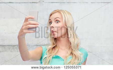 expressions, technology and people concept - funny young woman or teenage girl taking selfie with smartphone and making fish face over gray concrete wall background
