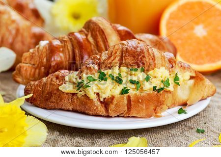Summer Morning Breakfast Croissant stuffed scrambled eggs, orange juicy. decorated with flowers.