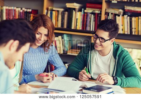 people, knowledge, education and school concept - group of happy students with books preparing to exam and writing in library