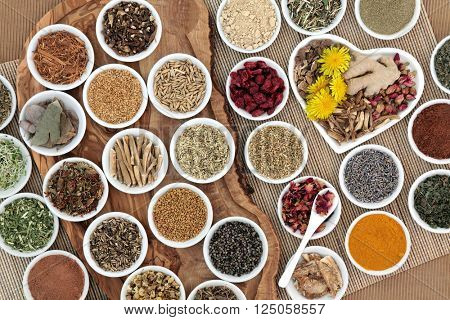 Large herb selection used in female alternative herbal medicine on an olive wood board over bamboo background.
