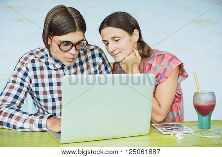 Surprised Young Nerd Couple In Glasses Looking At Computer Monitor While Sitting Together At The Lib