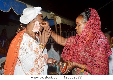 Abidjan, Ivory coast- February 26, 2015: Traditional rejoicing during the wedding ceremony in africa. The bride gives banknotes to her godmother.