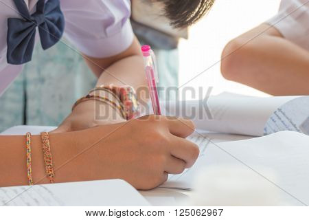 Thai students writing on a paper for Admissions in high school Thailand