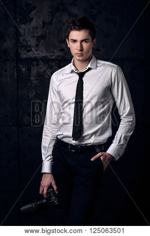 Strict portrait of photographer on black background