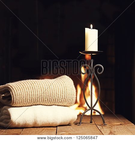 Warm Woolen Things And Candle In Candlestick Near Fireplace.
