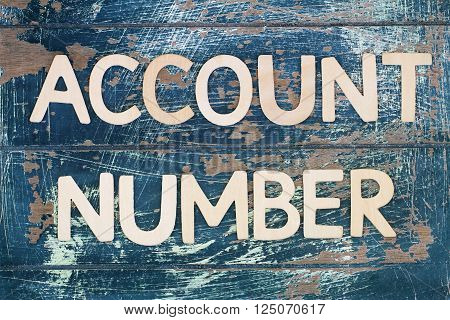 Account number written with wooden letters on rustic surface